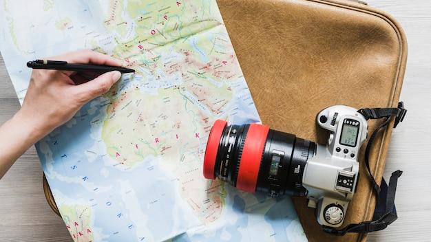 Une personne marquant la destination sur la carte au-dessus du sac de voyage