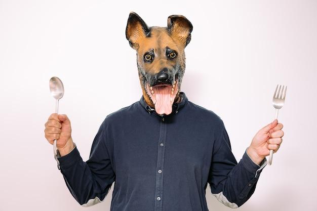Personne avec un masque de chien montrant une cuillère et une fourchette