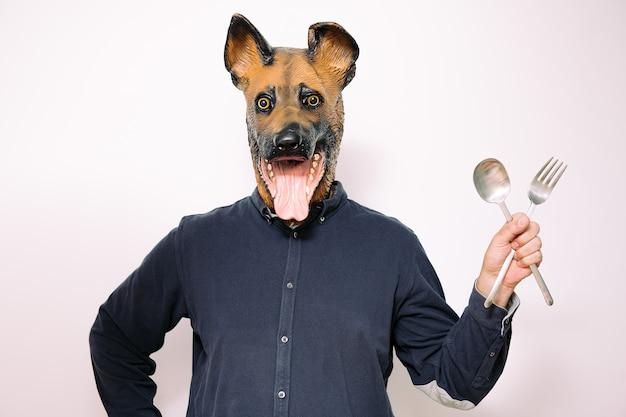 Personne avec un masque de chien montrant des ustensiles de cuisine