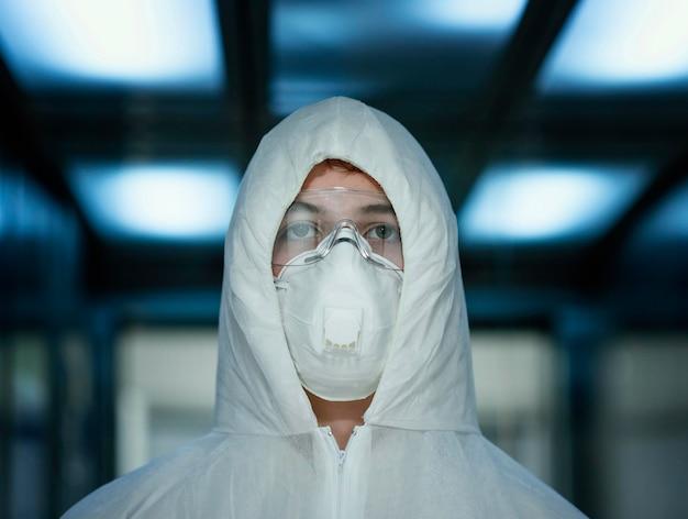 Personne avec masque facial portant un équipement de protection contre un risque biologique
