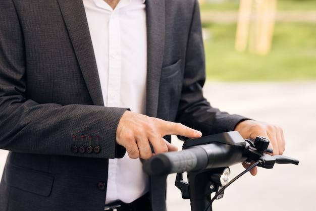 Une personne méconnaissable allume le scooter électrique l'homme active un scooter électrique une direction