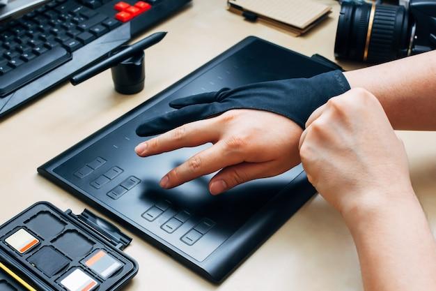 Personne méconnaissable portant un gant de protection pour utiliser la tablette graphique