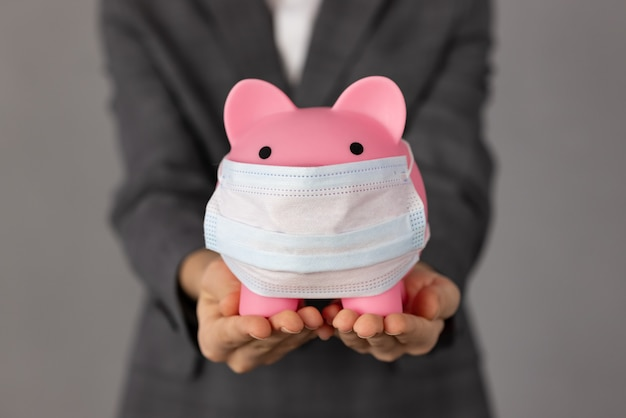 Personne méconnaissable tenant tirelire portant un masque de protection dans les mains. soutenir les entreprises pendant le concept de pandémie de coronavirus.