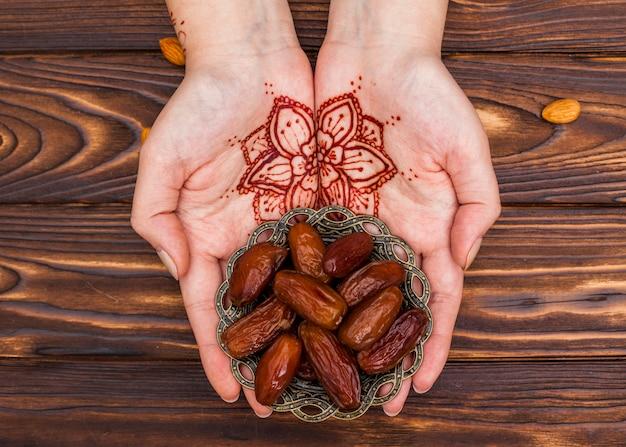 Personne avec mehndi tenant une assiette avec des fruits de dates