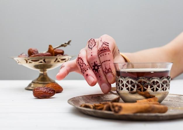 Personne avec mehndi tenant une tasse de thé sur la table