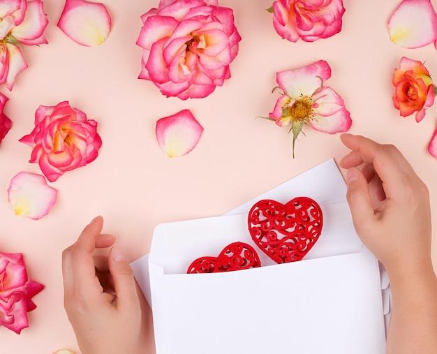Personne met un coeur rouge dans une enveloppe en papier blanc