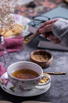 Une personne mettant la cassonade dans une tasse de thé