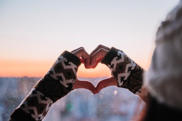 Personne montrant coeur par mains