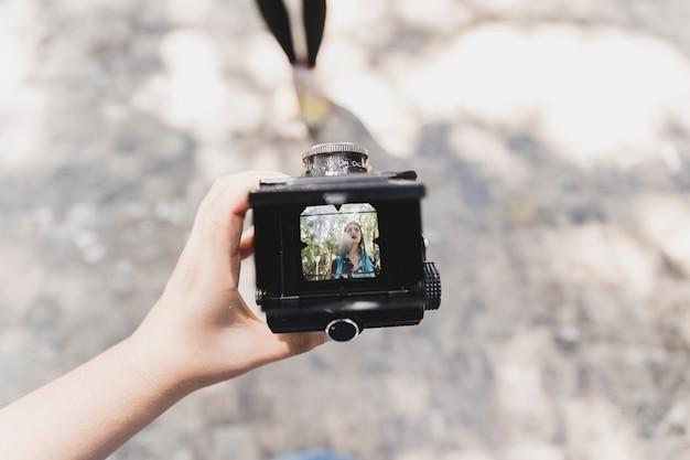Une personne montrant la photo d'une femme sur appareil photo vintage