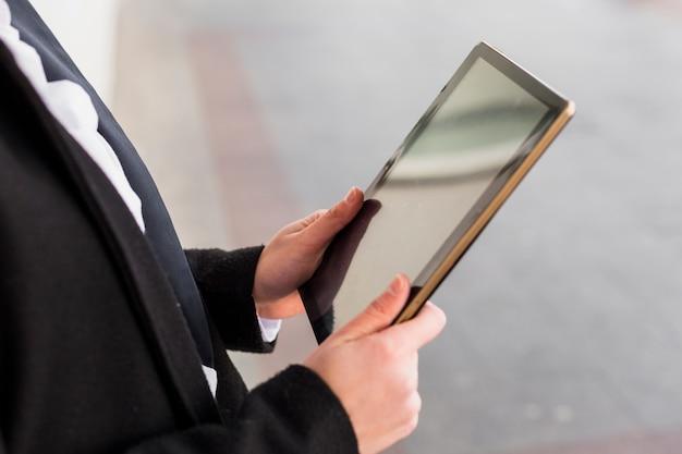 Personne en noir avec tablette à l'extérieur