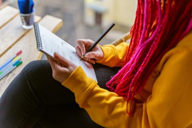 Personne non reconnaissable, fille artiste, illustratrice dessine dans un cahier, fait des croquis.