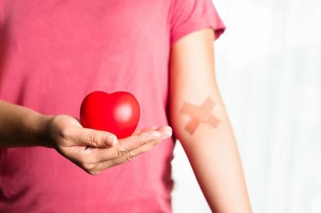 Une personne avec des plâtres croisés sur le bras tient un symbole dur sur la main
