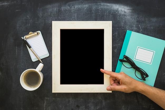 Une personne pointant le doigt sur le cadre photo avec papeterie et tasse à café sur le tableau