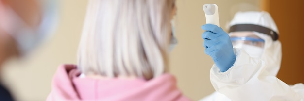 Une personne portant une combinaison médicale de protection et un masque mesure la température avec un thermomètre aux visiteurs