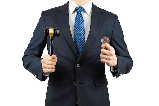 Une personne portant un costume et tenant un bitcoin à la main.