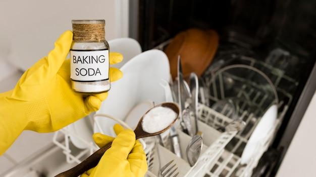 Personne portant des gants à l'aide de bicarbonate de soude dans un lave-vaisselle