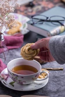 Une personne prenant un cookie tout en prenant un thé