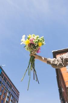 Personne en pull en tricot gris tenant un bouquet de fleurs