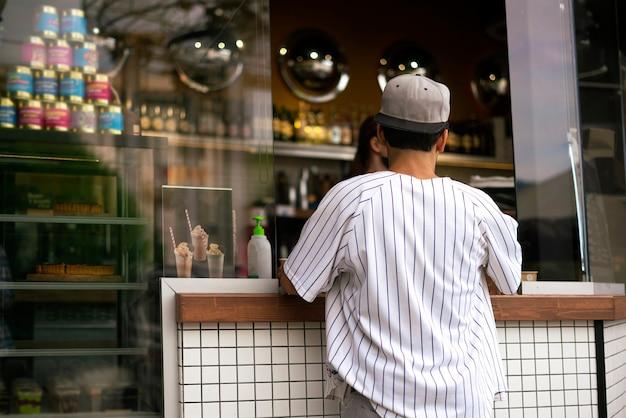 Une personne qui achète de la nourriture et du café dans un café de la rue de la ville