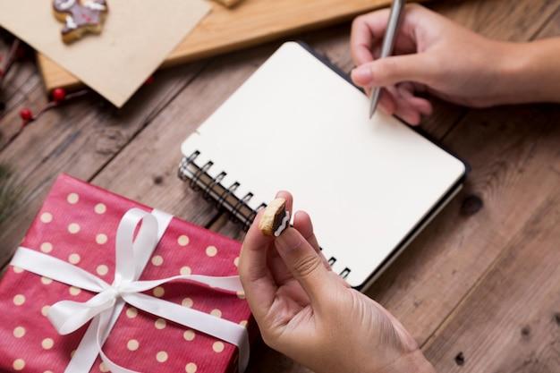 Personne qui écrit sur un cahier ouvert avec une boîte-cadeau et de délicieux biscuits faits maison de noël