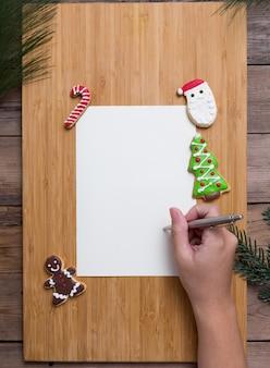 Personne qui écrit sur la carte de noël avec des biscuits faits maison