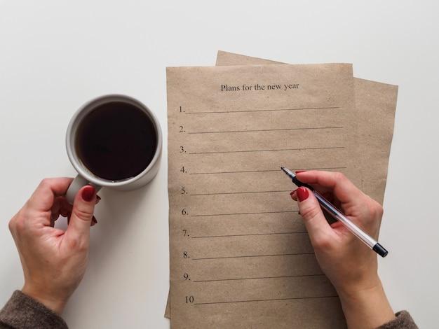 Personne qui écrit des plans pour la nouvelle année tout en buvant du café