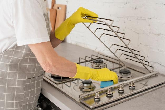 Personne qui lave la cuisinière avec des gants