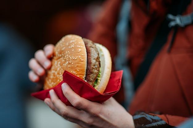 Personne qui mange un gros hamburger