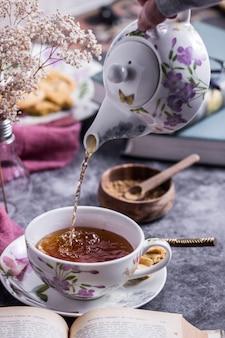 Une personne qui sert le thé avec une belle théière en lisant un livre