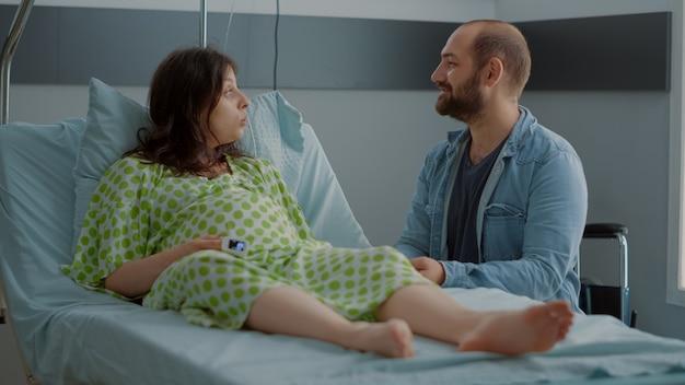 Personne de race blanche avec une grossesse assise avec un homme dans une salle d'hôpital