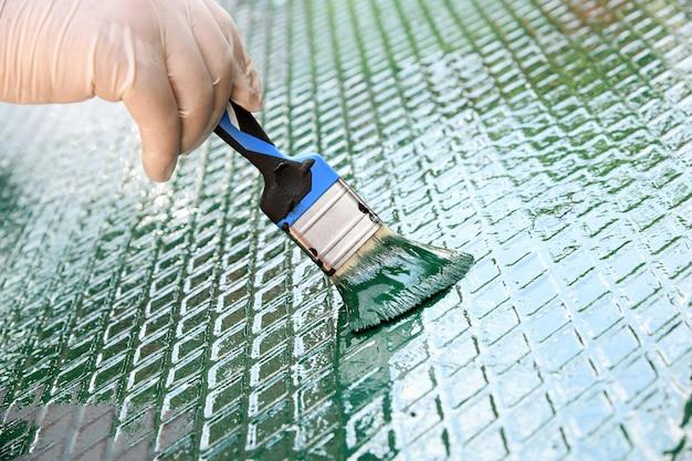 Personne rafraîchissant la peinture verte sur une grille métallique