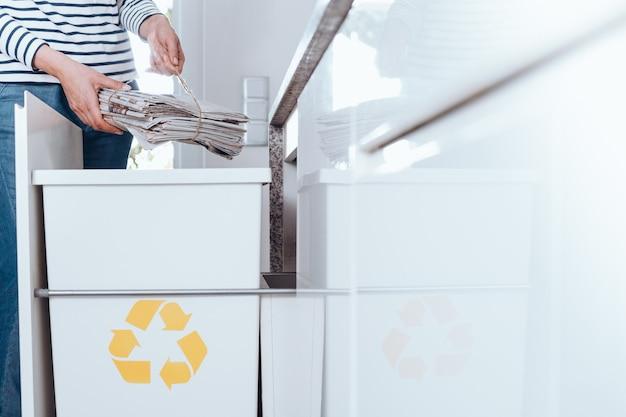 Personne responsable triant les déchets dans une cuisine moderne avec un bac spécial avec un symbole jaune pour le papier
