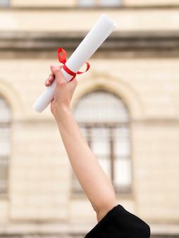 Personne en robe de graduation brandissant un diplôme