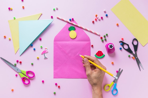 Une personne s'appuyant sur l'enveloppe avec des éléments décoratifs sur fond rose