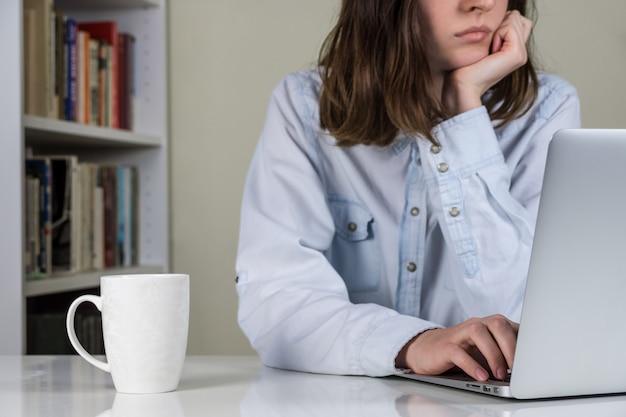 Personne s'ennuie travaillant à un ordinateur portable