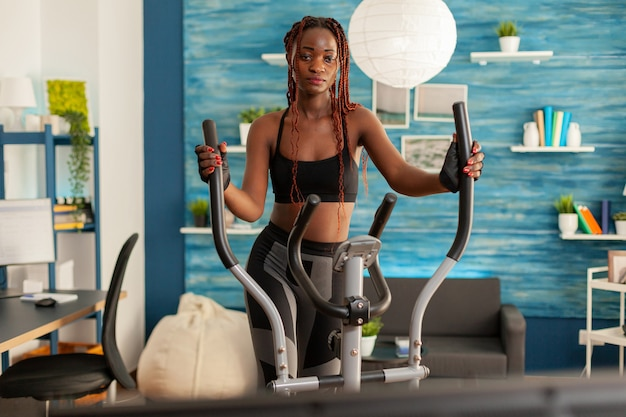 Personne s'entraînant dans le salon de la maison à l'aide d'une machine elliptique pour un entraînement cardio croisé, regardant des exercices en ligne