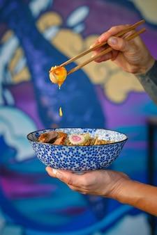 Personne sans visage de culture montrant des ingrédients de soupe de nouilles avec des baguettes au restaurant