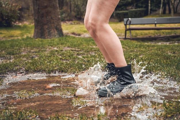 Personne sautant par-dessus une flaque d'eau dans le parc