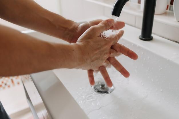 La personne se lave les mains dans le concept de santé et de protection de la salle de bain