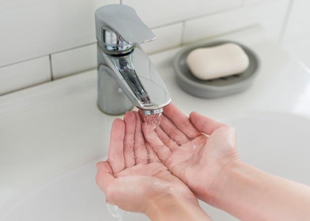 Personne se rinçant les mains avant de se laver avec du savon