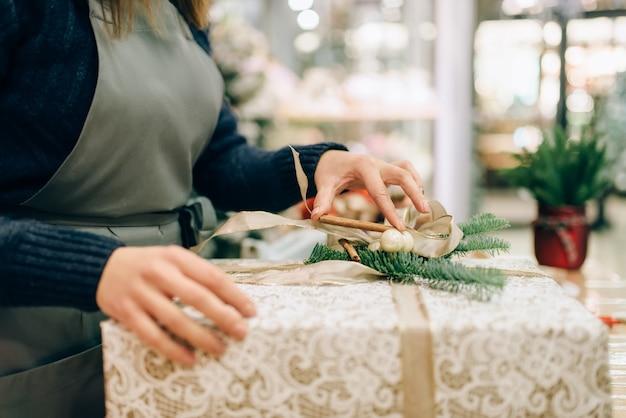 Personne de sexe féminin attache un arc d'or sur une boîte-cadeau