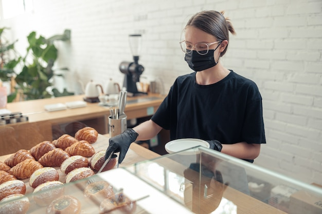 Personne de sexe féminin dans un masque de protection médical et des gants