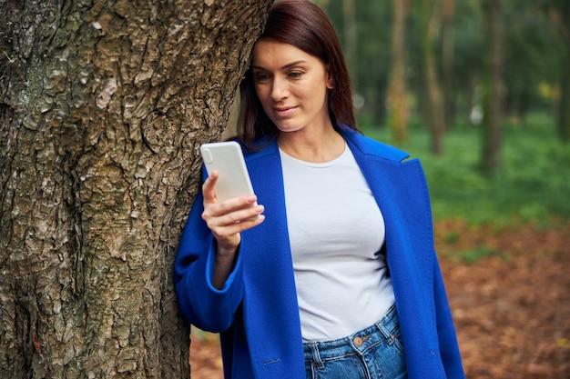 Personne de sexe féminin détendue s'appuyant sur l'arbre