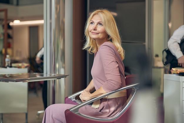 Personne de sexe féminin incroyable gardant le sourire sur son visage tout en visitant un salon de beauté pour faire une nouvelle coiffure