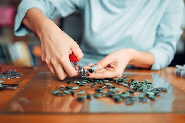Personne de sexe féminin mains avec des pinces, des bijoux faits à la main couture, fabrication de bijouterie
