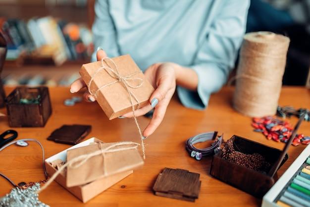 Personne de sexe féminin nouer un arc sur une boîte-cadeau, travaux d'aiguille