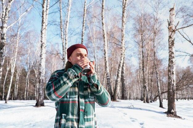 Personne de sexe masculin boit dans une tasse dans une forêt d'hiver enneigé. l'homme en chemise à carreaux détient une tasse de café à l'extérieur et profite du beau temps