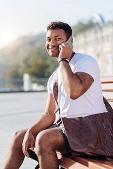 Personne de sexe masculin ravi positif gardant le sourire sur son visage et tenant le téléphone dans la main gauche alors qu'il était assis en position semi