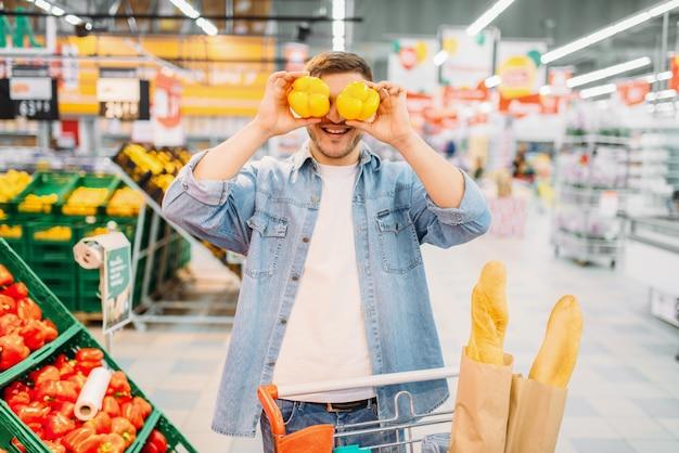 Personne de sexe masculin s'amuse avec des poivrons jaunes dans un supermarché, shopping familial. client en magasin, acheteur sur le marché