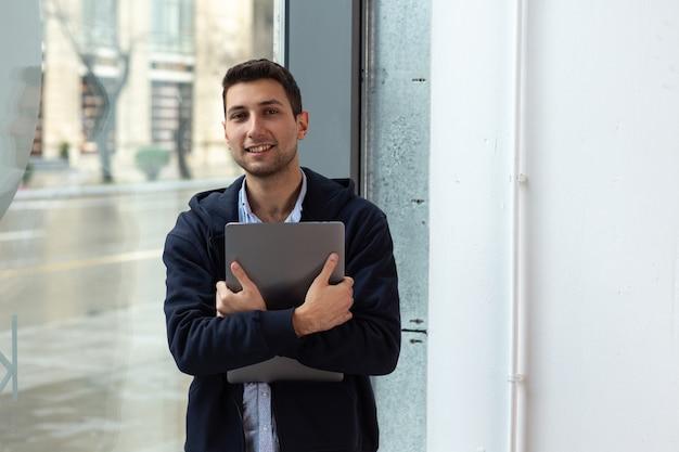 Une personne sourit tout en tenant un ordinateur portable